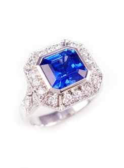 Sapphire engagement ring with a square emerald cut sapphire surrounded by a thread set millgrained diamond surround. Set in 18ct white gold with diamond set finely pierced millgrained shoulders.