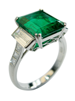 Emerald and diamond Art Deco style dress ring with handmade fine pierced detail inset, baguette diamond side stones and carre cut diamond shoulders.