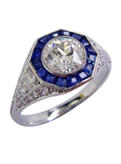 Handmade platinum art deco Diamond and sapphire dress ring. With calibre cut sapphires in an octagonal shape surrounding the center diamond, which is set in a fine mill grained setting.