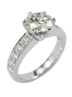 Solitaire diamond engagement ring. The center stone set with six claws and with pave set diamond shoulders.
