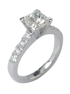 Four claw princess cut diamond engagement ring with sweeping up diamond cut down shoulders handmade  in 18 carat gold.