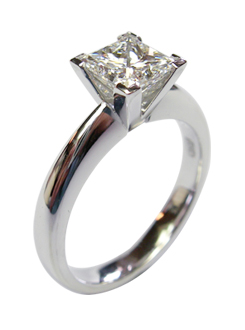 Four claw princess cut solitaire diamond engagement ring, handmade in platinum with V claws on the corners.