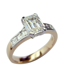 Emerald cut diamond engagement ring with trapezoid diamond shoulders and a soft rose gold shank.