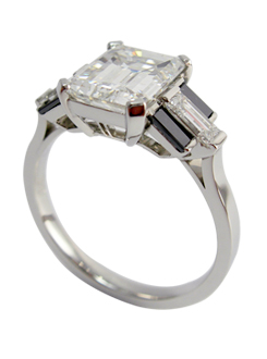 Emerald cut diamond ring Handmade in platinum with a very fine pierced detail and black diamond baguette shoulders.