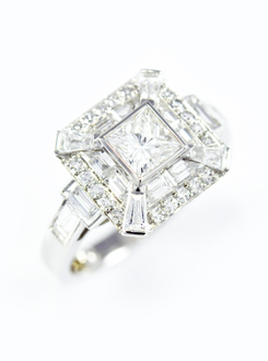 Princess cut diamond engagement ring with a double surround, a calibre cut baguette diamond surround and a single cut thread set surround, and tapered baguettes on the corners, all set in Platinum.