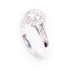 Diamond engagement ring with a diamond surround, finely millgrained in an art deco style.