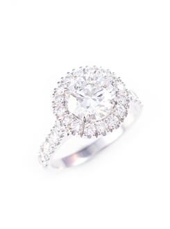 Platinum engagement ring with cut down diamond surround and a swept up diamond set shank.