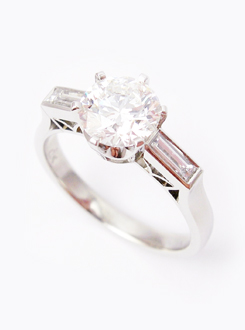 One carat diamond engagement ring set in 18 carat white gold with baguette shoulder stones. Handmade with fine detail inserts.