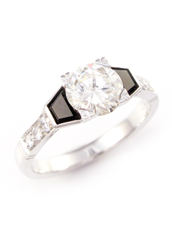 Diamond and onyx engagement ring set in 18ct white gold. The round brilliant center stone set into a square shape with trapezoid onyx shoulders and a diamond set band.
